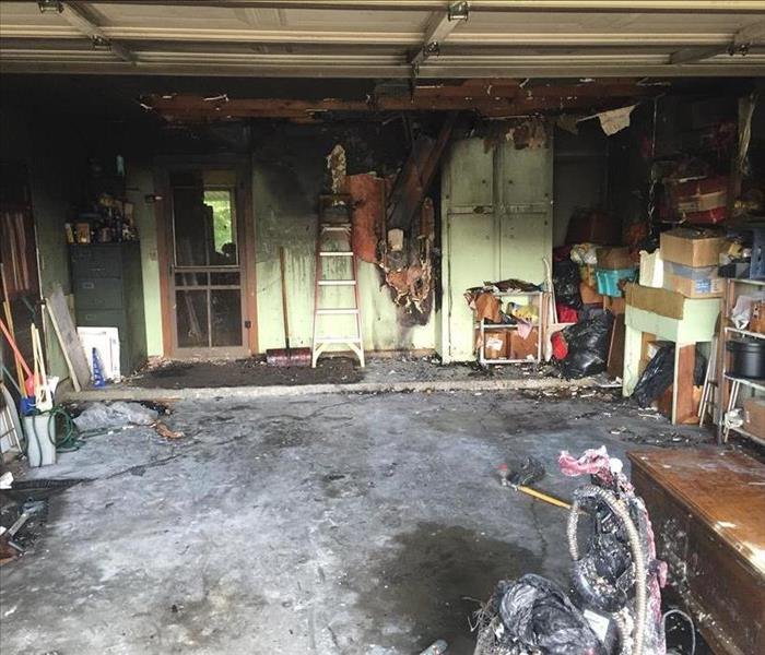 An open garage with significant fire damage and soot